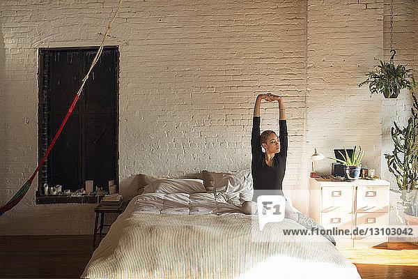 Junge Frau streckt die Arme aus  während sie zu Hause auf dem Bett sitzt