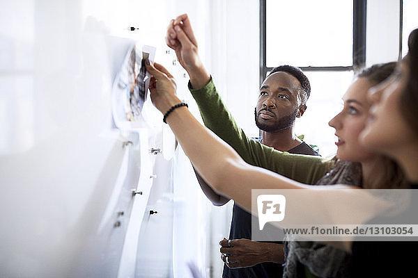 Seriöser Geschäftsmann betrachtet weibliche Kollegen  die Fotoausdrucke am Schwarzen Brett im Büro anbringen