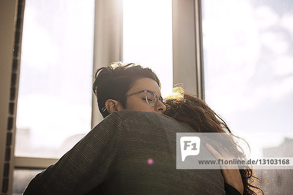 Lesbian couple embracing by window at home