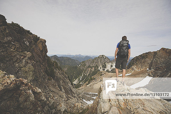 Hiker with backpack looking at view while standing on mountain against sky
