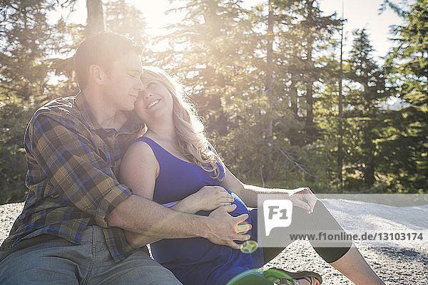 Mann berührt den Bauch einer schwangeren Frau  während er an einem sonnigen Tag an Bäumen sitzt