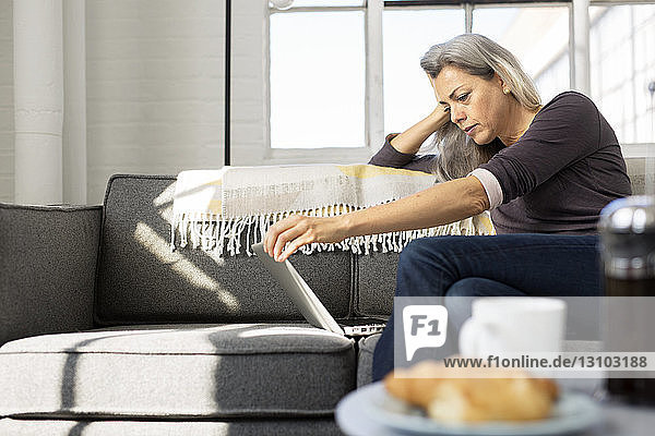 Low angle view of woman using laptop on sofa at home