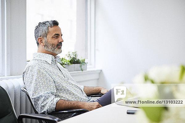 Geschäftsmann schaut weg  während er im Büro sitzt