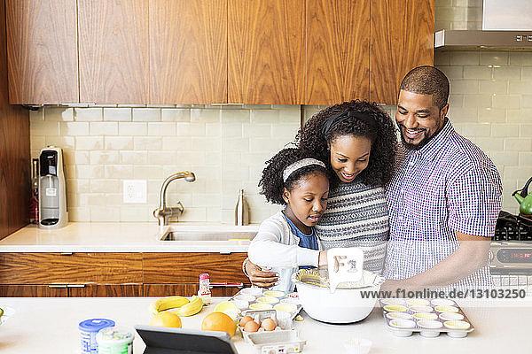 Eltern sehen Tochter beim Backen von Cupcakes in der Küche