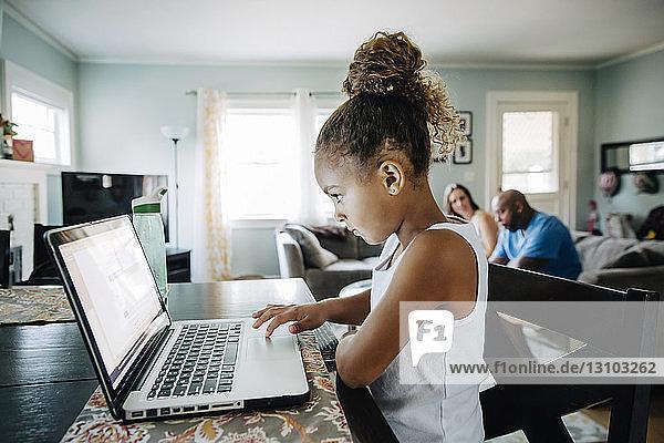 Seitenansicht eines Mädchens,  das einen Laptop benutzt,  während die Eltern im Hintergrund sitzen