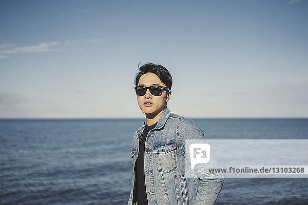Junger Mann trägt Sonnenbrille und Jeansjacke,  während er gegen Meer und Himmel steht
