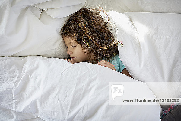 Hochwinkelansicht eines zu Hause auf dem Bett schlafenden Mädchens