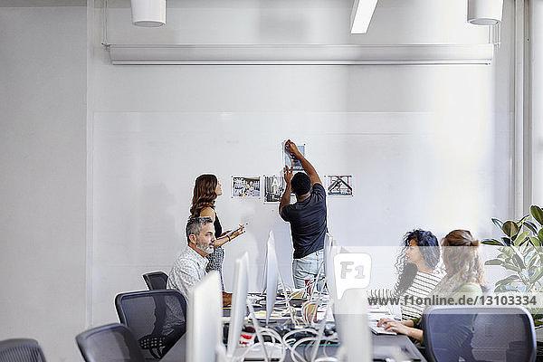Geschäftsleute diskutieren am Konferenztisch  während Kollegen Fotoausdrucke am Schwarzen Brett im Büro anbringen