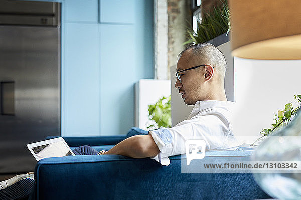 Side view of businessman using laptop while sitting on sofa at creative office