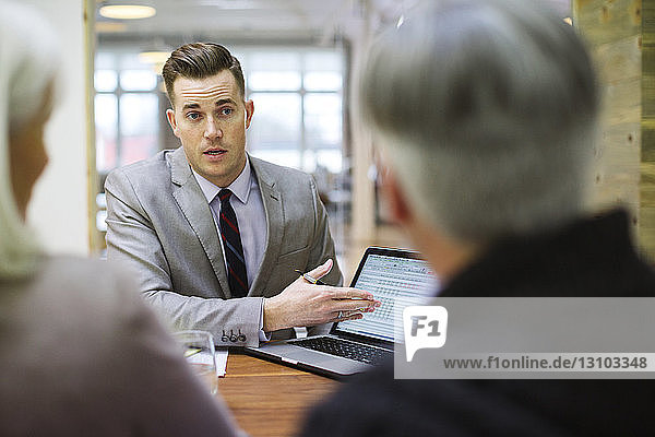Businessman explaining to colleagues over laptop computer in office