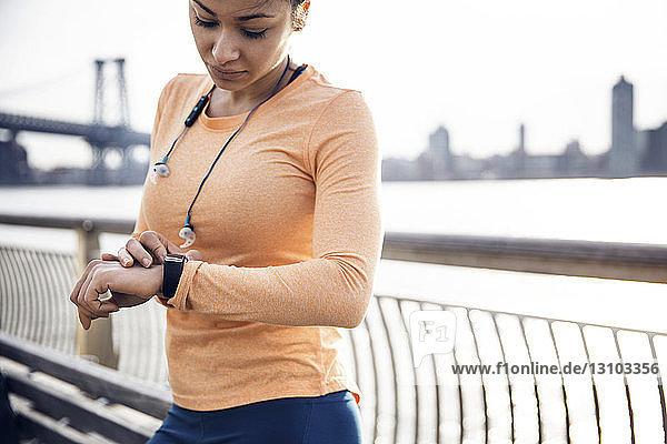 Weibliche Läuferin überprüft die Zeit  während sie auf dem Fußweg mit der Williamsburg Bridge im Hintergrund steht