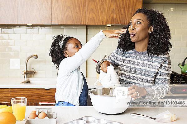 Verspielte Mutter und Tochter mischen in der Küche Teig mit dem elektrischen Schneebesen