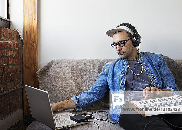 Man using laptop computer with piano at home