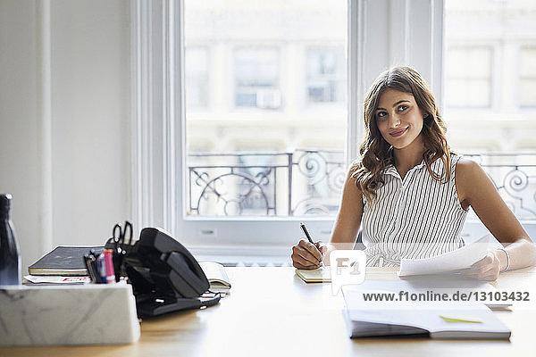 Lächelnde Geschäftsfrau schaut weg  während sie am Schreibtisch gegen das Fenster im Büro arbeitet