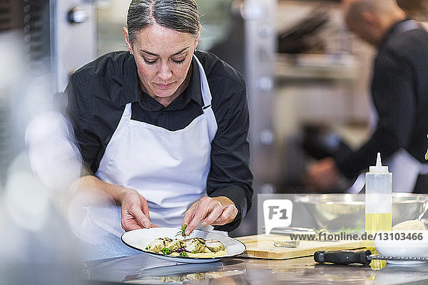 Female chef garnishing food while coworker working in background at restaurant