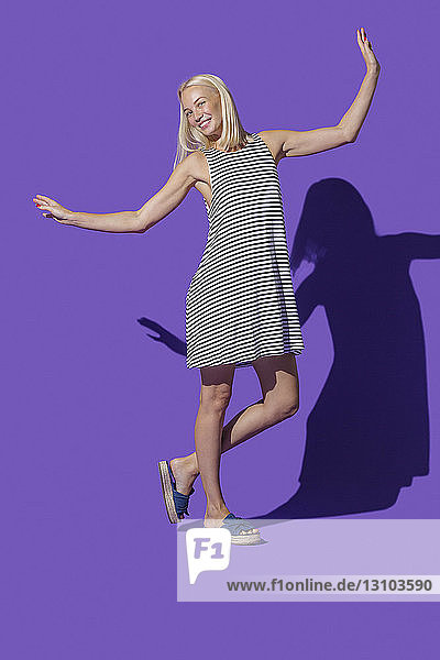Portrait carefree woman in striped dress against purple background