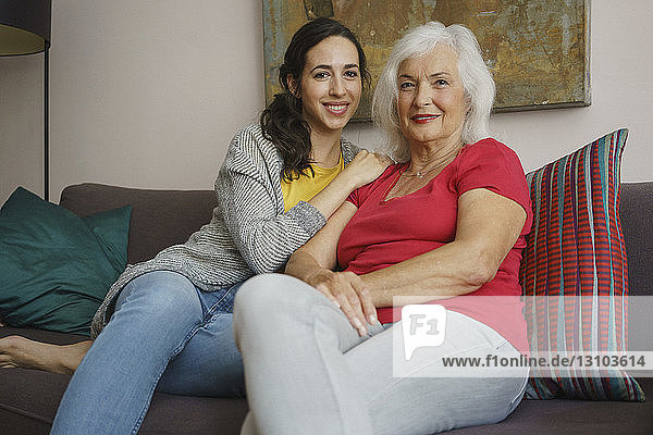 Portrait smiling senior mother sitting with daughter on living room sofa