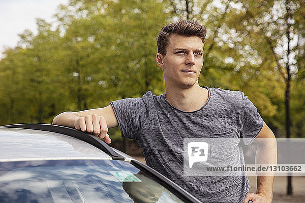 Portrait young man leaning on car  looking away