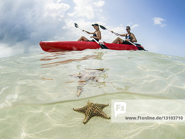 Couple kayaking on ocean at Starfish Beach  Grand Cayman  Cayman Islands Couple kayaking on ocean at Starfish Beach, Grand Cayman, Cayman Islands