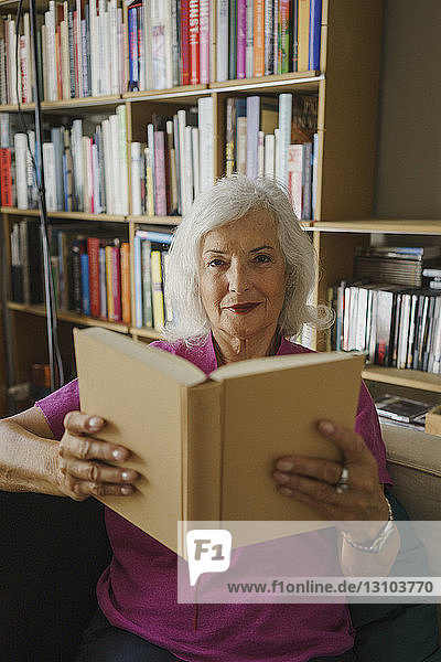 Portrait confident senior woman reading book