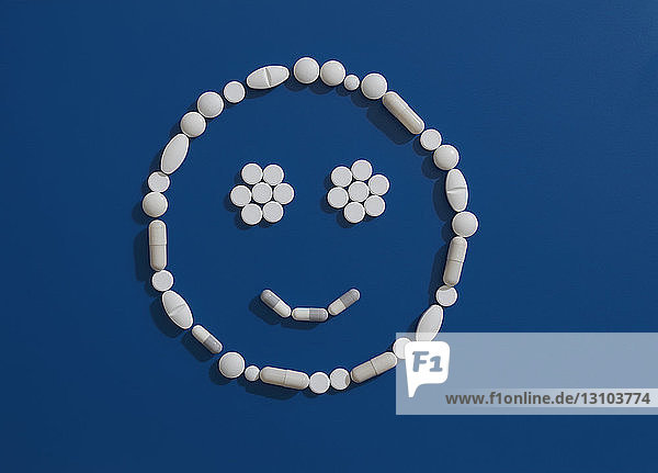 Pills forming smiley face on blue background