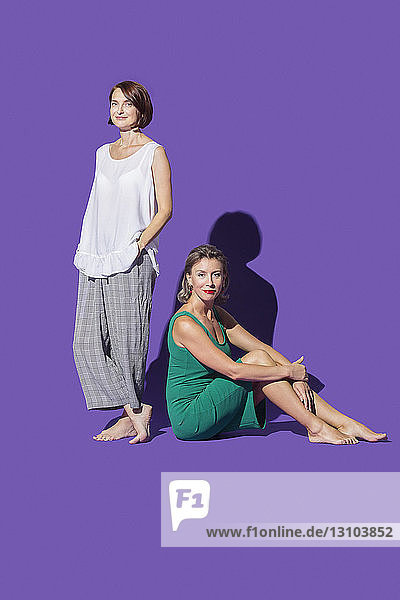 Portrait confident  barefoot women against purple background