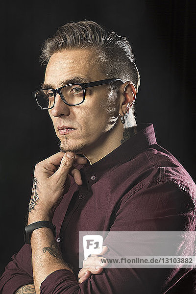 Portrait of serious man wearing glasses and looking away against black background