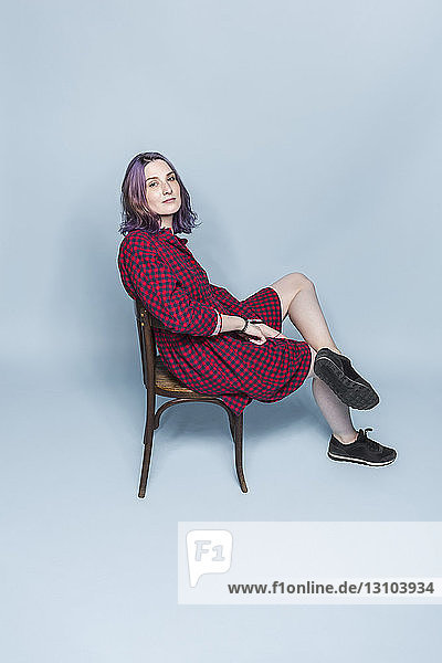 Portrait confident and fashionable young woman sitting on chair against blue background
