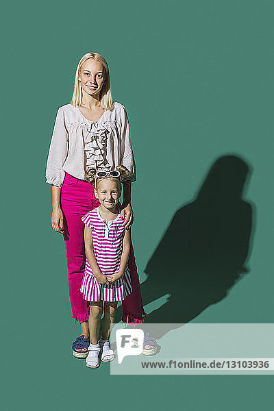 Portrait smiling mother and daughter against green background