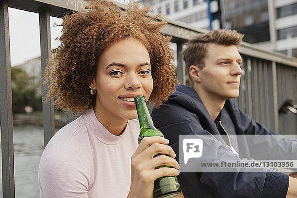 Portrait young woman drinking beer on urban bridge