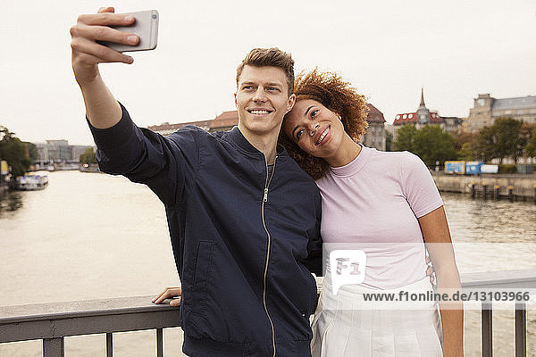 Affectionate young couple with smart phone taking selfie on urban bridge