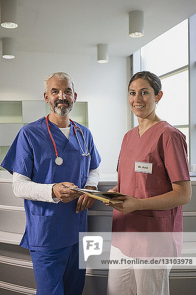 Portrait confident doctors with medical record in hospital
