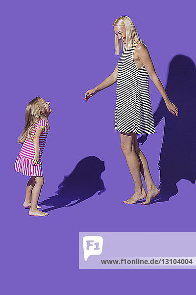 Carefree mother and daughter in striped dresses dancing against purple background