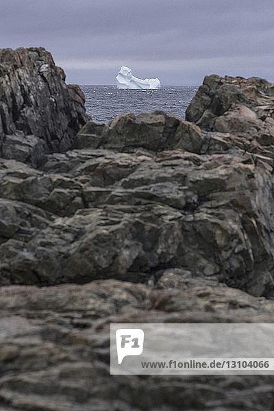 View of iceberg in sea through rocks on shore  Fogo Island  Newfoundland  Canada View of iceberg in sea through rocks on shore, Fogo Island, Newfoundland, Canada