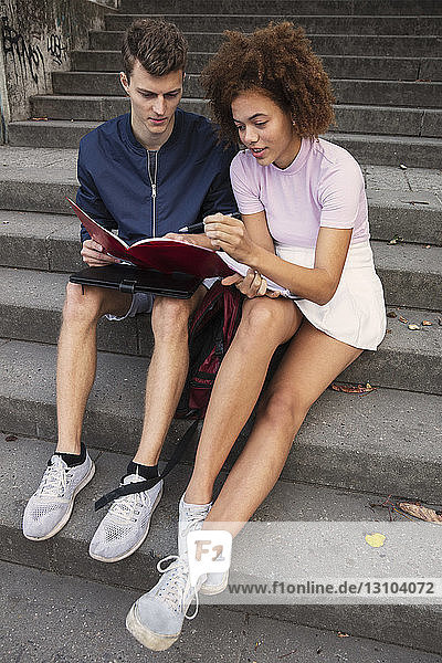 Young couple reviewing paperwork on steps