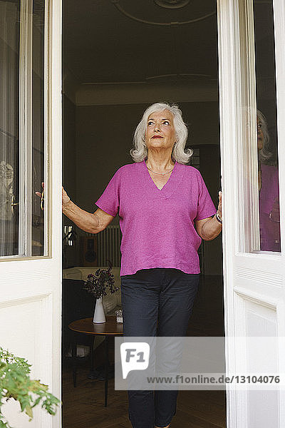 Thoughtful senior woman standing at patio doorway