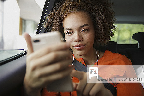 Young woman listening to music with headphones and mp3 player in car