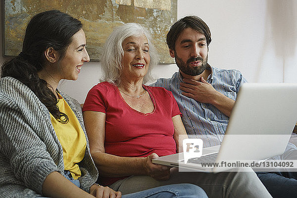 Senior mother using laptop with daughter and son on living room sofa