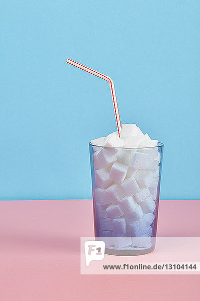 Glass filled with sugar cubes and straw