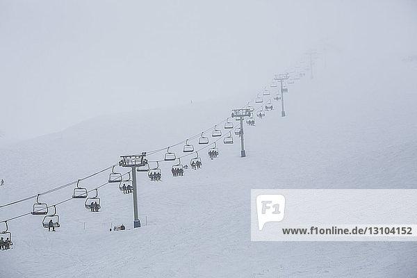 Skiers riding ski resort chair lift up mountainside