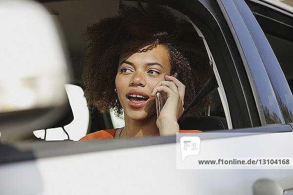 Young woman talking on smart phone and driving car