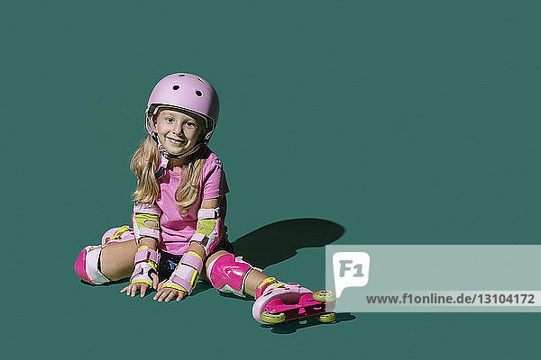 Portrait smiling girl roller skating on green background