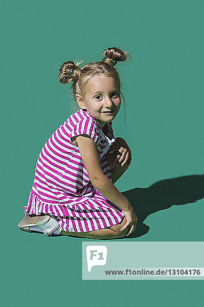 Portrait smiling girl against green background
