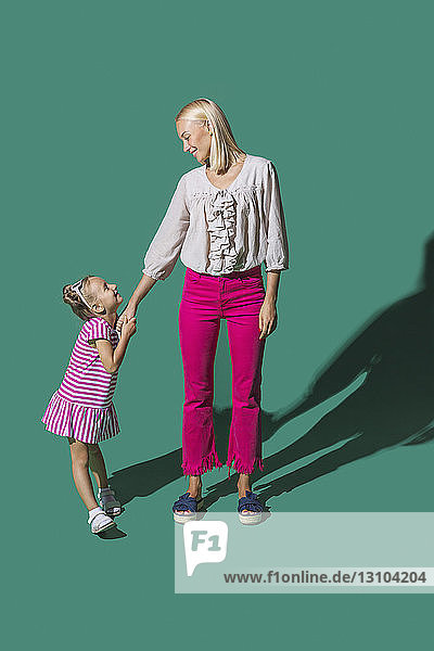 Mother and daughter holding hands on green background