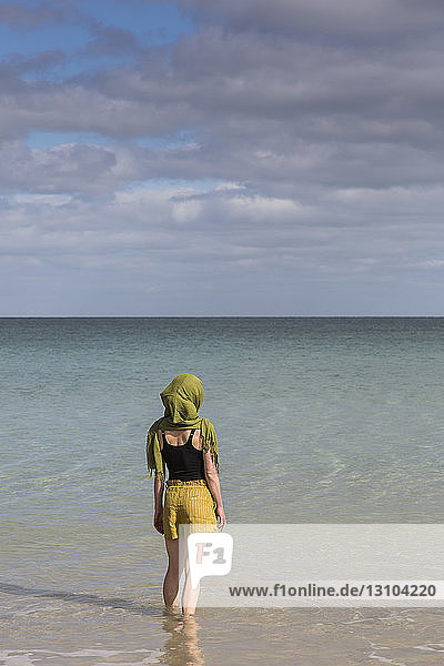 Serene woman with headscarf wading in sunny ocean