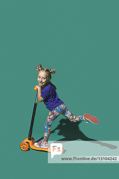 Playful girl riding scoter on green background