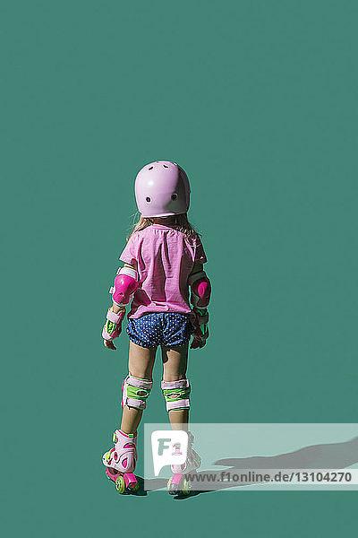 Girl roller skating on green background