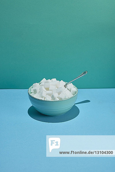 Bowl filled with sugar cubes and spoon