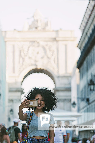 Young woman with smart phone taking selfie with Rua Augusta Arch  Lisbon  Portugal
