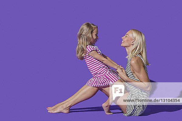 Mother and daughter in striped dresses on purple background
